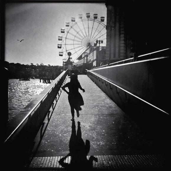 """""""Das Foto unten beruht auf einem schlichten Reflex. Ich hörte die Frau und ihren Freund rufen, sie rannten, um eine Fähre zu erwischen. Ich drehte mich um, löste aus und hatte Sydneys bekannten Luna Park im Hintergrund."""""""
