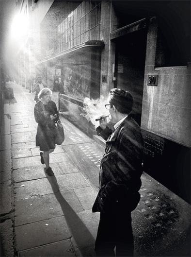 """Die Nostalgie Bei dieser Aufnahme ging es dem Fotografen nicht allein um die kontrastreichen Lichtverhältnisse. """"Die Kleidung der Passantin und der Verkäuferin, die kurz zum Rauchen nach draußen gegangen ist, hat etwas Nostalgisches. Das Bild könnte auch zu einer ganz anderen Zeit entstanden sein, wären dort nicht das Smartphone der einen und die E-Zigarette der anderen Frau."""" Edwards hat sie mit dem iPhone abgelichtet. © Bredun Edwards"""