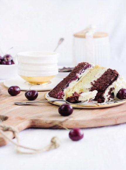 """Schwarzwälder Kirschtorte: nicht der Kuchen im Ganzen, sondern nur ein Stück, quer gelegt und """"angegessen"""". Das gibt dem Bild mehr Leben. Dazu noch eine Tasse Kaffee im Hintergrund, passend zum Kuchen, und hier und da ein paar Kirschen."""