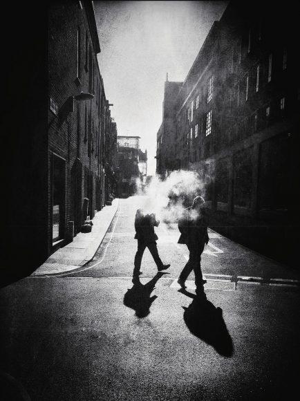 """Street Photography bedeutet nicht selten, etwas Wartezeit zu investieren, um den richtigen Augenblick abzupassen oder die Entwicklung einer Szene abzuwarten. Gut, wenn man – wie Bredun Edwards – gerade sowieso anstehen muss, um einen Kaffee zu bestellen. """"Ich hatte die beiden Männer und ihre Rauchwolke die ganze Zeit im Blick"""", erinnert sich der Fotograf. """"Sie machten offensichtlich Mittagspause und gönnten sich noch eine Zigarette, bevor sie zurück an den Schreibtisch mussten. Leider passte das Licht die ganze Zeit nicht. Erst als sie aufbrachen, um zurück ins Büro zu gehen, bekam ich das Motiv, das ich mir gewünscht hatte."""" Neben den Rauchschwaden sind es die hohe Mittagssonne und Fluchtlinien der Straßen, die das Bild perfektionieren."""