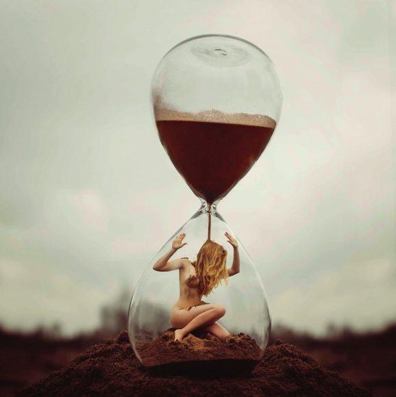 Out of time: eine Frau, gefangen in der Zeit, hinter gläsernen Wänden, in einer Sanduhr. Sie versucht auszubrechen, heraus aus den Fängen der Zeit. Heraus aus der bedrückenden Enge ihres gläsernen Käfigs. Weg von der erdrückend über ihr zerrinnenden Zeit. || f/7,1 | 1/50 s | ISO 200