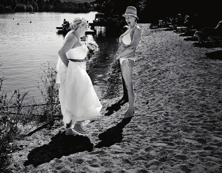 """RICHTIGER RIECHER: Eigentlich war Steven schon ein paar Meter vorausgeeilt, als er aus dem Augenwinkel die Strandbesucherin wahrnahm, die zum Gratulieren auf die Braut zusteuerte. """"Oft habe ich in solchen Momenten schon das Gefühl, dass sich etwas entwickeln könnte"""", beschreibt der Fotograf. """"Das klappt nicht immer, aber ich suche mir meinen Bildausschnitt und nehme meist eine Serie auf, bis der perfekte Augenblick da ist."""" Der Hochzeitsfotograf agiert im Stil eines Street-Fotografen. Die markanten Schatten und der hohe Kontrast - beides provoziert von der Sonne bei fast 40 Grad - bieten sich für eine Schwarz-Weiß-Umwandlung besonders an. Überdies kommen das Brautkleid und der weiße Bikini umso besser zur Geltung. f/4 / 1/1.000 s / ISO 100 / Canon 4/17-40 mm @40 mm (© Steven Herrschaft)"""