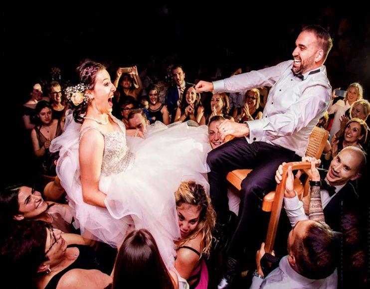 """PARTY-TIER: Wer Steven bucht, bekommt eine Bildergeschichte von früh bis spät – tanzender Fotograf inklusive. """"Ich kann gar nicht genau sagen, wie ich das mache"""", lacht der Student. """"Aber ich stehe nicht einfach daneben, sondern gebe bei der Party selbst Gas. Irgendwie habe ich dann immer noch eine Hand für die Kamera und eine für den Blitz frei."""" Der Blickwinkel und die Emotionen sprechen für sich. Um nach einem langen Hochzeitstag noch derart fit zu sein, treibt Steven jeden Tag eine Stunde Sport. f/4 / 1/200 s / ISO 1.250 Canon 4/17-40 mm @17 mm. (© Steven Herrschaft)"""