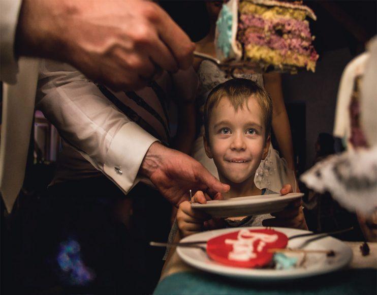 """KREATIVE VARIANTE: Klar, auch Steven Herrschaft muss darauf achten, dass er den Tag über alle wesentlichen Augenblicke festhält. Solide Standardfotos von Klassikern wie dem Tortenanschnitt müssen sein. Doch danach fängt der Spaß für den Südhessen erst richtig an: Er darf das Experimentieren beginnen. """"Kindern zu folgen führt häufig zu besonderen Momenten"""", hat er erlebt. In diesem Fall brachte ihm der tortenlüsterne Junge eine weitere Auszeichnung der """"Fearless Photographers"""". f/4 / 1/160 s / ISO 2.000 / Canon 4/17-40 mm @24 mm (© Steven Herrschaft)"""