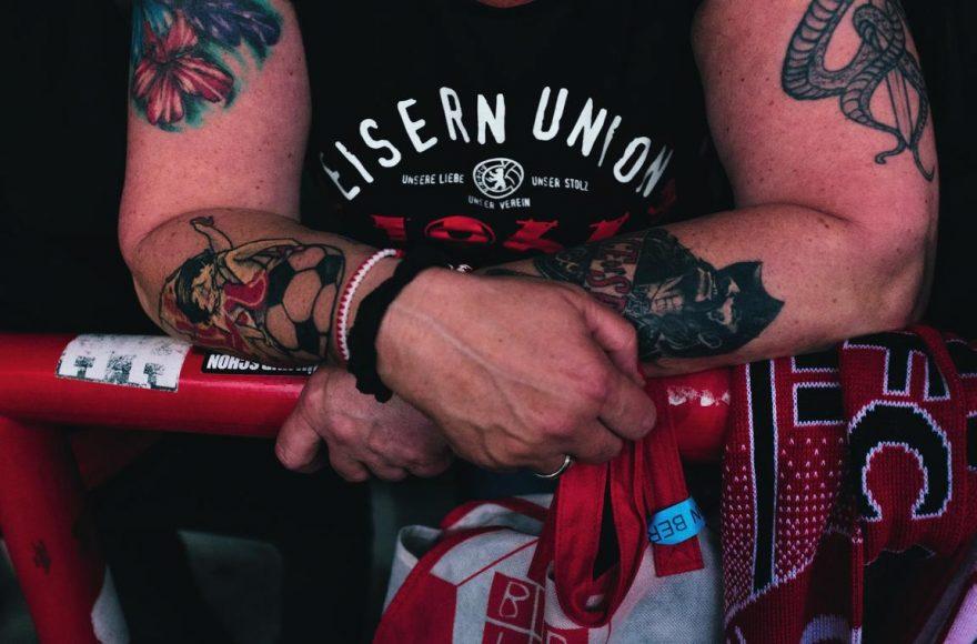 Krasse Typen begleiten den 1. FC Union Berlin. Nur wer genau hinsieht, erkennt die floralen Tattoos des weiblichen Fans. Auch hier setzt der Fotograf die Anonymität bewusst ein. Er spielt mit den Kontrasten der blumigen Farben und der kräftigen Arme. || f/2,8 | 1/200 s | ISO 1.600