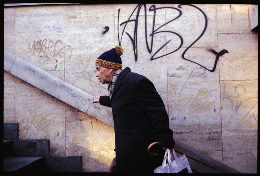 Inhaltliche Konflikte und formale Parallelitäten wecken unser Interesse. Es geht aufwärts, dennoch wirkt der Herr gebrechlich. Er bewegt sich gegenläufig der Sehrichtung, tatsächlich führt die Linie von links oben nach rechts unten abwärts. Der Passant scheint vom Leben gezeichnet, so wie der Zahn der Zeit sich auch auf der Wand abzeichnet.