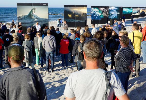 Ray Collins vor seiner riesigen Open-Air-Installation am Strand anlässlich des Umweltfotofestivals Horizonte Zingst. Bis zum 3. Juni können diese Monumente der Naturgewalt in dem Kurort an der Ostsee besucht werden. (© A. Spaeth)