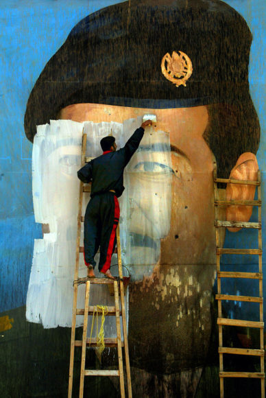 """Carolyn Cole, """"An image of Saddam Hussein, riddled with bullet holes, is painted over by Salem Yuel. Symbols of the leader disappeared quickly throughout Baghdad soon after US troops arrived in the city and took control. Baghdad, Iraq, April 2003"""". © Carolyn Cole/Los Angeles Times"""