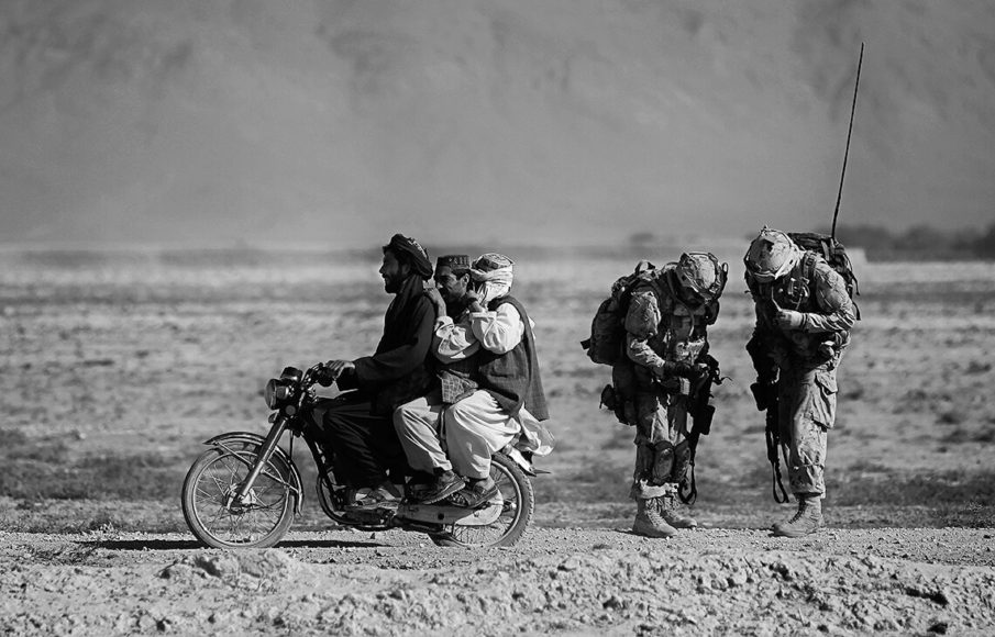 """Anja Niedringhaus, """"Afghan men on a motorcycle overtake Canadian soldiers with the Royal Canadian Regiment during a patrol in the Panjwaii district, southwest of Kandahar, Salavat, Afghanistan, September 2010"""". © picture alliance/AP Images"""