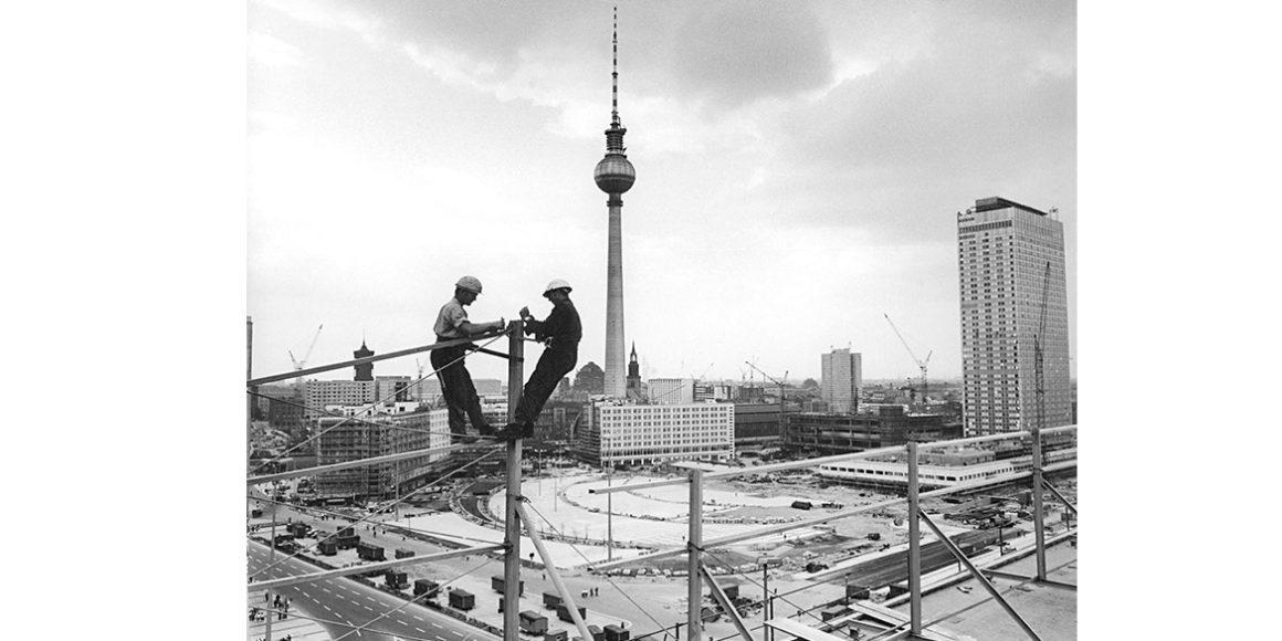 """Bauarbeiten bei Montagearbeiten an der Leuchtschrift auf dem """"Haus der Statistik"""", 13 August 1969 © Bundesarchiv (183-H0813-0026-001)  Foto: Eva Brüggmann"""