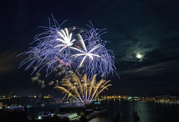 Tipp 1: Schaffen Sie einen lokalen Bezug Um das Feuerwerk aus der Beliebigkeit des reinen Effekts herauszulösen, kann das Umfeld wie hier in Wilhelmshaven gezielt eingebunden werden. Die Szenerie des Hafens und der Mond hinter den Wolken rahmen das Feuerwerk ein und geben dem Motiv Halt. Nikon D700 / 32 mm KB / ISO 200 / f/16 / 15 s