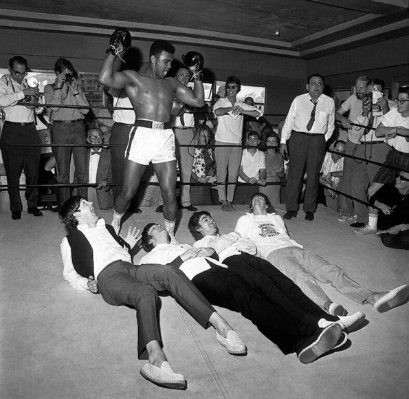© Harry Benson, 1964, Ali Stands Over Beatles Hands Up