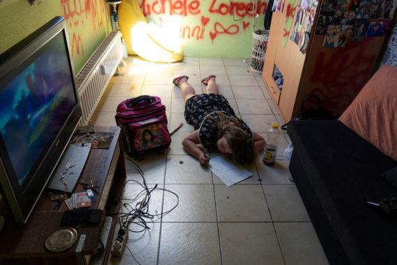Kind macht Hausaufgaben auf dem Boden