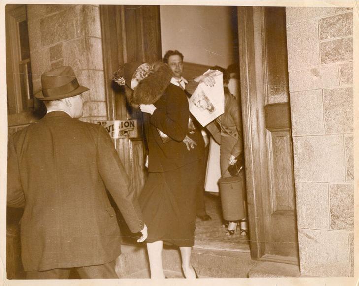 Zwei Frauen verlassen eine Polizeistation und verdecken ihre Gesichter. New York, 1937. © Weegee / International Center of Photography