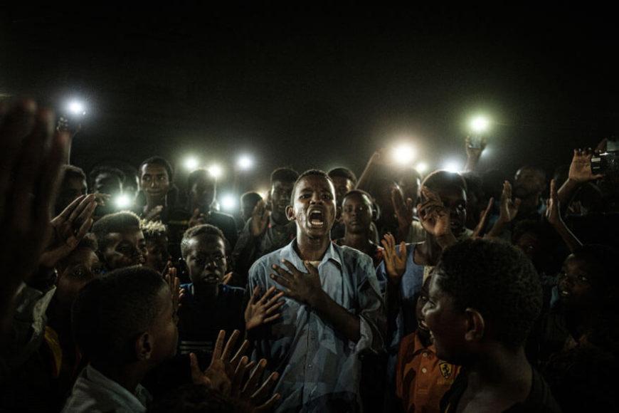 """World Press Photo of the Year. Yasuyoshi Chib. """"Straight Voice"""".  Agence France-Presse.   (Kamera: Fujifilm X-H1) Unbeugsam zeigen sich diese sudanesischen Demonstranten: Obwohl Behörden den Strom abgeschaltet haben, marschieren sie unter Lebensgefahr gegen die Militärherrschaft und für mehr Zivilrecht durch die Straßen, beleuchtet von ihren Smartphones. ...  Am 17. August 2019 regelte ein Abkommen schließlich die Aufteilung der Macht zwischen Zivilbevölkerung und Militär."""