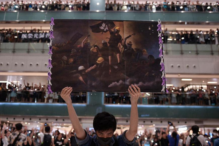 """1. Platz Story of the Year. Nicolas Asfouri. """"Hong Kong Unrest"""". Agence France-Presse. (Kamera: Nikon D5) """"Glory to Hong Kong"""" singen die Menschen von den Balkonen im Stadtteil Shatin. Es ist das Protestlied gegen die Vereinnahmung vonseiten des chinesischen Festlandes, zu dem dieser junge Mann heroisch das Plakat in die Höhe streckt. Die Massenproteste in Hong Kong zeig-ten der Welt wie geschlossen und stark demokratisch geprägte Gesell-schaften gegen die Zersetzung auftreten können. Riesige Straßenzüge waren von Menschen geflutet. Und auch bei diesem Volksaufstand stand ein junger Mensch an der Spitze: der Student Joshua Wong.  … Am 23. Oktober wurde das Auslieferungsge-setz zurückgenommen."""