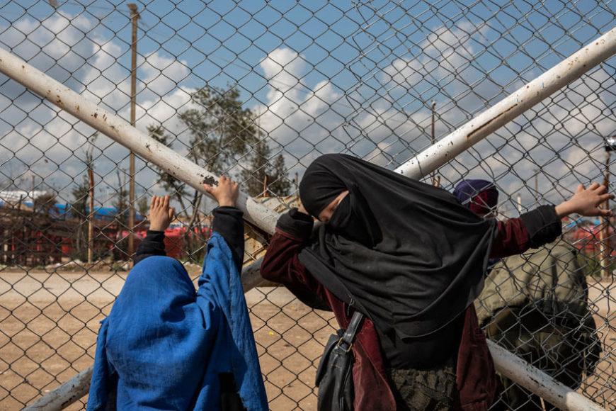 """3. Platz General News, Stories. Ivor Prickett. """"ISIS and its Aftermath in Syria"""".   Für The New York Times. (Kamera: Canon EOS 5D Mark IV)  Im Internierungslager Al-Hol nahe der syrisch-irakischen Grenze. Eine Mutter wartet auf Einlass in einen anderen Bereich der Anlage, wo sie sich mit Lebensmitteln versorgen muss. Sie zählt zu den Vergessenen eines Krieges, deren menschliche Tragödie Ivor Prickett auf stille Weise ein Gesicht gibt wie mit diesem an die bibli-sche Kreuzigung erinnernden Motiv. Als sich der IS aus Nordsyrien zurückzog, kamen Zehntausende Menschen aus den Enklaven, darunter viele Frauen und Kinder. Zahlreiche IS-Kämpfer haben sich erge-ben oder wurden gefangen genommen.  … Für die Kurden stellte sich die Frage: Was tun mit so vielen Gefangenen, von denen viele unter 18 Jahre alt sind, verwaist oder von ihren Familien getrennt wurden?"""