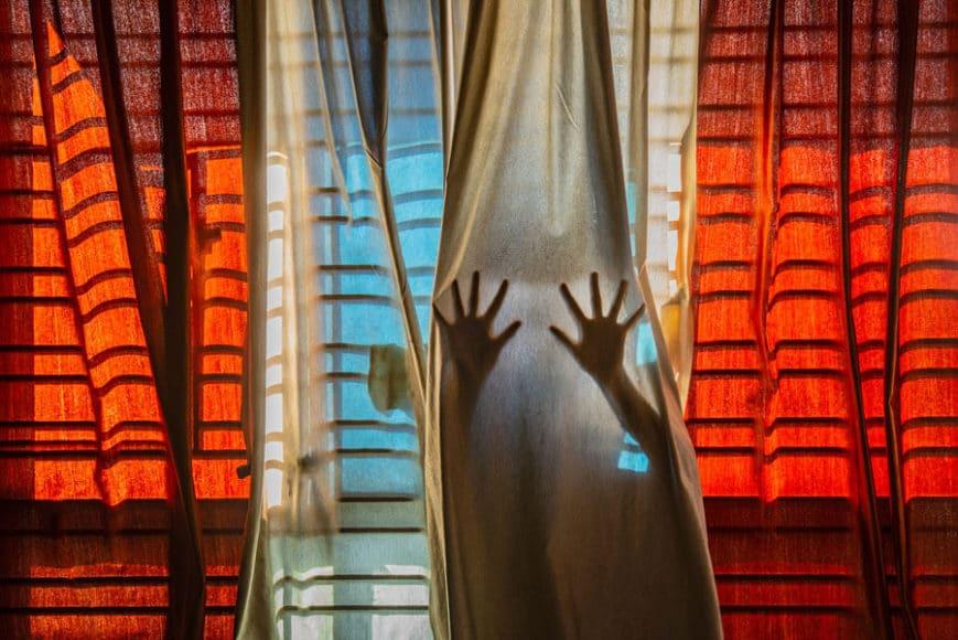 """Wichtig ist den Initiatoren des Wettbewerbs Sony World Photography Awards auch der Nachwuchs. Pubarun Basu aus Indien überzeugte mit seiner Vision: """"Ich habe dieses Bild geschaffen, um das Gefühl wiederzugeben, in einem Moment oder in der eigenen Realität gefangen zu sein. Ich sah die Vorhänge als die Stoffe des Raum-Zeit-Kontinuums, aus denen diese beiden Hände nicht ausbrechen können. Der Schatten, den die parallelen Geländer auf den Stoff werfen, vermittelt auch den Eindruck eines Käfigs, in dem das Wesen für die Ewigkeit gefangen ist."""" © Pubarun Basu, India, Shortlist, Youth, Composition and Design, 2021 Sony World Photography Awards."""