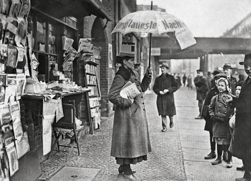 Zeitungshändlerin – mit Faschingshütchen und Reklameschirm – vor ihrem Zeitungsstand, 1920. © bpk / Kunstbibliothek, SMB, Photothek Willy Römer / Willy Römer.