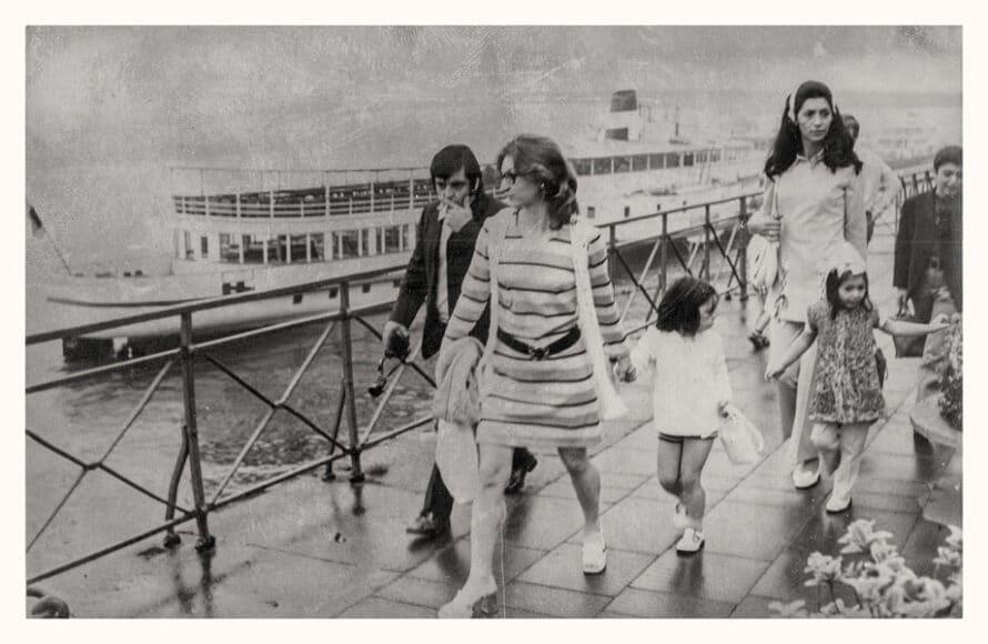"""Necla Türköz mit Tochter Alpin, Sohn Ugur und Freund*innen auf einer Rheinfahrt  Köln, um 1972.  """"Ich kann mich erinnern, dass es diese Schifffahrten gegeben hat. Das war ein Ereignis, weil alle Familien zusammengekommen sind. Mein Vater hat auch immer wieder Musik gemacht. Am Anfang haben alle, die Musik machen konnten, die ganze Gesellschaft unterhalten; das war toll."""" (Alpin Harrenkamp)  © Alpin Harrenkamp ."""