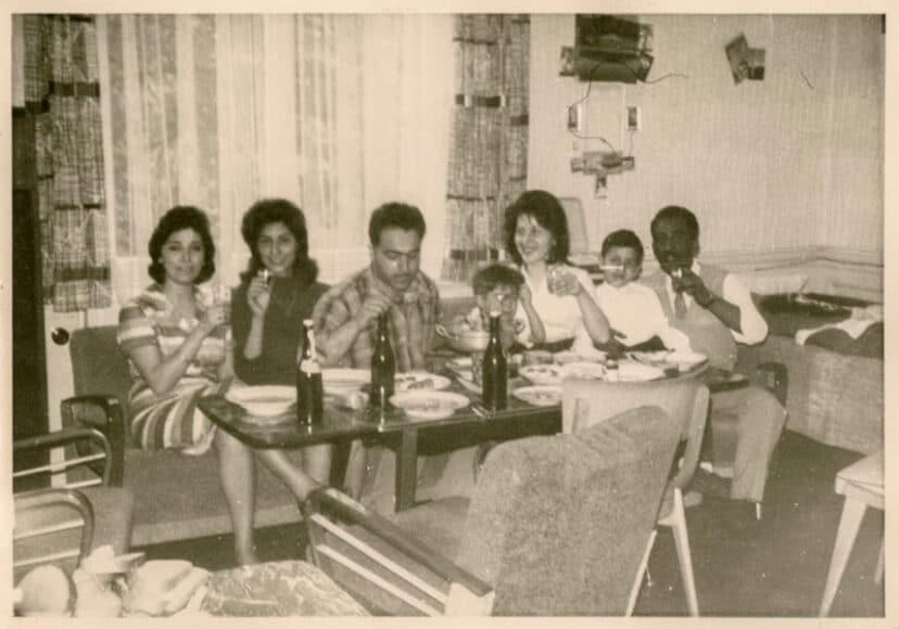 """Die Familien Türköz und Ücgüler in der ersten gemeinsamen Wohnung, Köln, Agnesviertel, Merlostraße, 1963.  V. 1. n. r.: Freundin der Familien, Necla und Metin Türköz mit ihrem Sohn Ugur, Sevim und Fikri Üc;;güler mit ihrem Sohn Fikret """"Samstags wurde oft gekocht. Unsere Zimmer waren ganz kleine Räume. Es gab nur eine Küche, die man geteilt hat, und das war eine Wohnküche. Jeder hat etwas gekocht, dann hat man sich zusammengesetzt und gegessen."""" (Fikret Ücgüler) © Alpin Harrenkamp."""