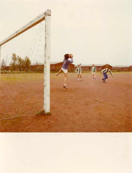 """Mitat Özdemir als Tormann auf dem Fußballplatz, im Hintergrund die Klöckner-Humboldt-Deutz-Wohnbaracken, Köln-Poil, 1971.  """"Ich war verantwortlich für Sport und hatte ein Fußballteam namens Efes gegründet. Hier bin ich Tormann während eines Trainings. Um 1971 fand an diesem Ort ein Turnier zwischen den KHD- und Ford-Wohnheimen statt. Unser Team hat gewonnen. Der damalige Direktor der Ford-Werke hat mir die Trophäe überreicht, da ich sowohl Mannschaftskapitän als auch Betreuer war. Im Ford-Magazin wurde darüber berichtet. Das hat mich sehr gefreut, weil es das erste Mal war, dass mein Foto in einer Zeitschrift erschienen ist."""" (Mitat Özdemir)  © Mitat Özdemir."""