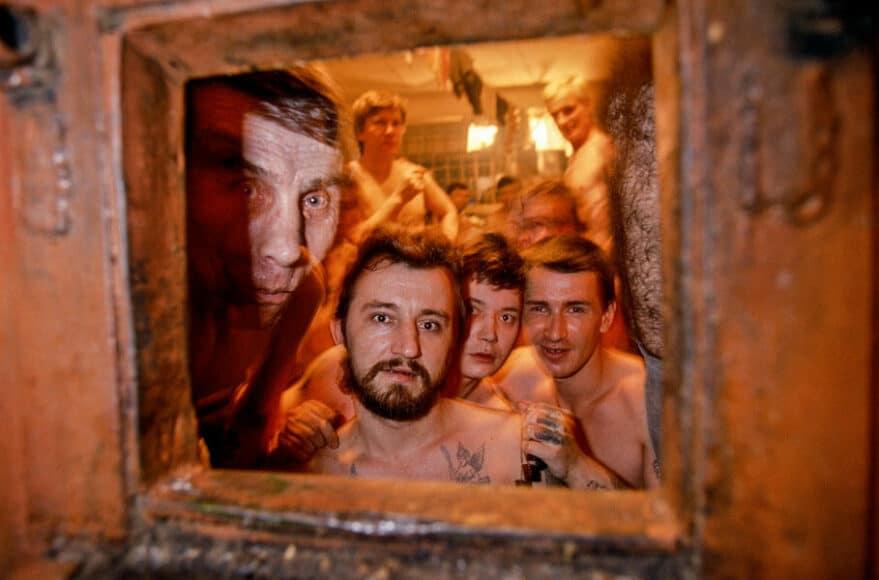 """The Cross Gefängnis, St.Petersburg, 1991, © Hans-Jürgen Burkard. Besonders gefährliche Häftlinge, Mitglieder der berüchtigten St. Petersburger Banden, schauten bei der Verteilung ihres Mittagessens neugierig hinter der Klappe in der Zellentür hervor. Das St. Petersburger Untersuchungsgefängnis """"IZ 45/1"""", genannt """"Das Kreuz"""", wurde schon zu Zeiten der Zaren am Ufer der Newa gebaut. Die Häftlinge in hoffnungslos überfüllten Zellen warten manchmal jahrelang auf einen Prozess."""