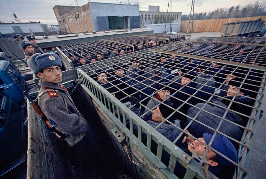 """The Human Cage - Bahnstation Sima, Sibirische Eisenbahn, 1989, © Hans-Jürgen Burkard. Frühmorgendlicher Transport zur Arbeit im Straflager Nr. 272/32, Station Sima, an der Transsibirischen Eisenbahn. Kategorie: """"Strenges Regime"""". Diejenigen, die nach zehn oder fünfzehn Jahren in den Lagern entlassen werden, können nirgendwo hingehen und nirgendwo bleiben und haben keine Chance, echte Arbeit zu finden. Fast alle von ihnen kehren früher oder später zurück."""