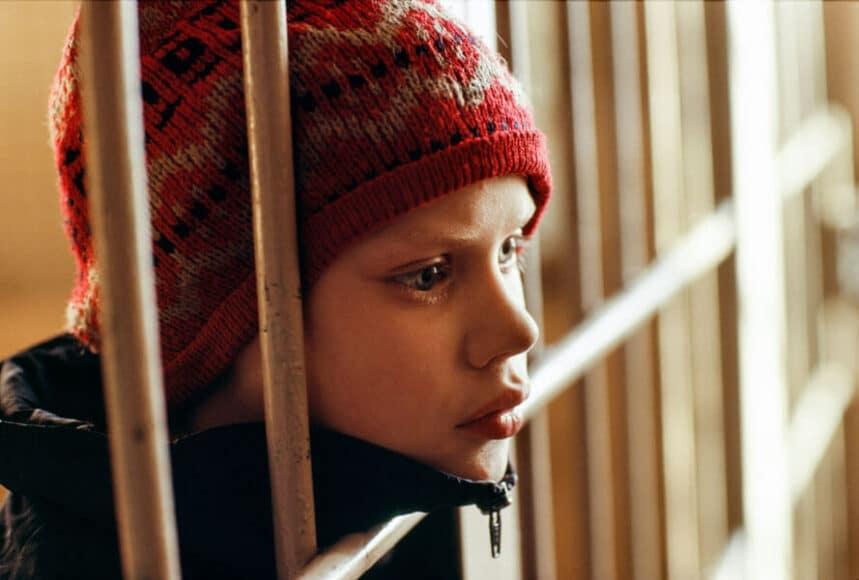 """In Gewahrsam, Portrait eines Jungen und mehrfachen Mörders, 1994, © Hans-Jürgen Burkard. Der Junge und seine Schwestern lebten auf dem Puschkin-Platz in Moskau. Sie spezialisierten sich darauf, Betrunkene zu überfallen, die auf schneeglattem Boden ausgerutscht und hingefallen waren. Sie schlugen ihnen mit Ziegelsteinen auf den Kopf, bis sie sich nicht mehr bewegten und raubten sie aus. Auf diese Weise ermordeten sie mindestens vier hilflose Menschen. Die Polizei hatte Wolodja in Gewahrsam genommen - er wartete auf seine psychisch kranke Mutter, die ihn """"freilassen"""" wollte."""