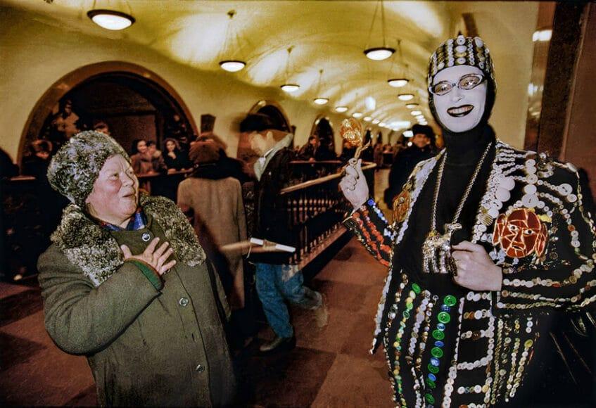 In den Gängen der Metro, Moskau, 1993, © Hans-Jürgen Burkard. Kleine Freuden für die Menschen. In den dunklen Gängen der Moskauer Metro schenkt der Designer Andrei Bartenev sein strahlendes Lächeln. Und sein Anzug mit gewagter Knopfleiste kommt auch bei der Bäuerin aus der russischen Provinz gut an.