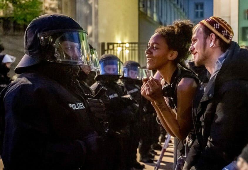 """Demonstration am 1. Mai 2013, Berlin, © Hans-Jürgen Burkard. Die jährliche, fast schon ritualisierte Demonstration zum 1. Mai in Berlin, hier 2013. Dies war mein erstes Foto für die Deutschland-Serie. Ich war den ganzen Weg des Protestzugs von Kreuzberg bis """"Unter den Linden"""" mitgelaufen. Erst als die Teilnehmer, kurz vor dem Hotel Adlon, von Polizisten in Darth Vader-Ausrüstung gestoppt und kurzzeitig eingekesselt wurden, entstand dieses Bild, das mich an eine Foto-Ikone von Marc Riboud erinnert: ein Mädchen mit Blume in der Hand vor Bajonetten; beim """"Peace March"""" in Washington D.C. 1967."""