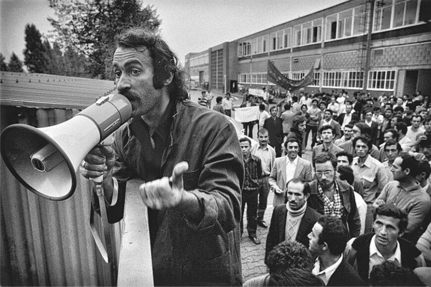 """Baha Targün mit Megafon am Werkstor, im Hintergrund Streikende. Aus der Serie """"Ford-Streik"""", Köln, 1973. © Gernot Huber."""