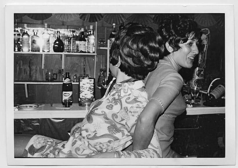 """Chrysaugi Diederich mit einer Freundin bei einer Party, Köln, um 1965.  """"Der Verlobte meiner Freundin hat uns ein Apartment besorgt, das teilten wir mit noch zwei deutschen Mädchen Das war schön. Wir hatten eine große Küche, Freiheit und vor dem Haus war ein wunderschöner Platz mit Kirche wir hatten unsere Clique. Wir gingen tanzen. Im Rheinpark. Da war dann Livemusik."""" (Chrysaugi Diederich) © Chrysaugi Diederich/DOMiD-Archiv, Köln."""